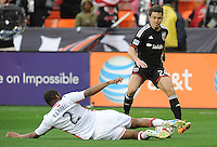 Washington, D.C.- March 29, 2014. Lewis Neal (24) of D.C. United goes against Andrew Farrell (2) of the New England Revolution. D.C. United defeated the New England Revolution 2-0 during a Major League Soccer Match for the 2014 season at RFK Stadium.