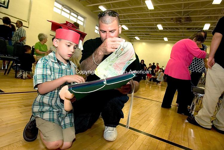 TORRINGTON, CT--07 JUNE 2007--060707JS20--Jeriel Munoz, 5, of Torringtin, shows his father Rey Munoz (Rey is CQ) his scrapbook during the YMCA kindergarten Graduation held Thursday at the Northwest YMCA in Torrington. <br /> Jim Shannon/Republican-American