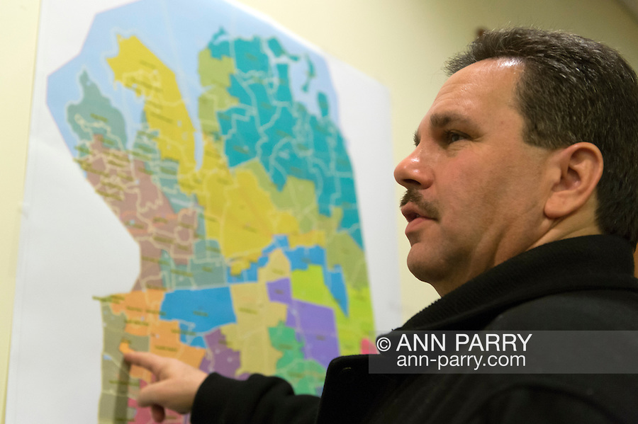 January 3, 2013 - Mineola, New York, U.S. - PATRICK NICOLASI of Elmont, NY, points to the Republican Commissioners' Proposed map, which did not include street names, on the back wall of Nassau County Legislature Chambers. The Nassau County Districting Advisory Commission held a night time meeting on two Redistricting maps for the 19 Legislative Districts, one proposed by Republicans, one by Democrats. In the standing room only chambers, dozens shared their views with the commission during the Public Comment segment. After a brief recess, the commission voted at 10:40 PM for each map, neither of which passed. By January 5 it must complete its work for the Nassau Legislature, which must pass a Redistricting map by March 5, 2013.