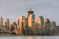 The sunrise colored sky is reflected off of the building facades in lower Manhattan, including the World Financial Center and Battery Park City.  The rising One World Trade Center (Freedom Tower) is in the background.