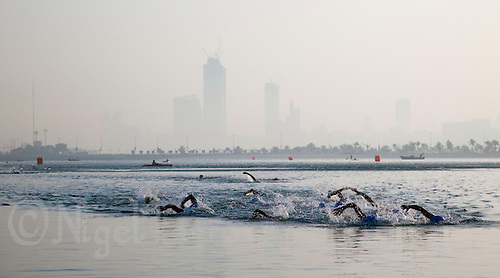 13 MAR 2010 - ABU DHABI, UAE - The elite mens field approach the shore for the turn at the end of the first lap of the swim at the Abu Dhabi International Triathlon (PHOTO (C) NIGEL FARROW)