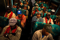 Sugar cane cutters sit on a bus while going to work on a plantation near Florida, Valle del Cauca, Colombia, 27 May 2012. The Cauca River valley is the booming centre of agriculture and sugar cane cultivation in Colombia. Although the main part of the crop is still refined into a sugar, the global demand of biofuel and ethanol has intensified the sugar cane production in the last years. 85 percent of Colombia's cane crop is still harvested the manual way, employing approximately 30,000 workers. Working six days a week, under harsch labor conditions, the sugar cane cutters earn $4 for every ton of cane they cut, with no access to social benefits due to the tricky system of intermediary contractors and cooperatives.