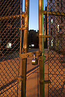 AVAILABLE FROM JEFF AS A FINE ART PRINT.<br /> <br /> AVAILABLE FROM PLAINPICTURE FOR COMMERCIAL AND EDITORIAL LICENSING.  Please go to www.plainpicture.com and search for image # p5690214.<br /> <br /> Mysterious Urban Scene - Buildings at Dusk Viewed Thru Chain Link Fence, Lower Manhattan, New York City, New York State, USA