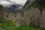 Old castle walls against a dramatic background of clouds and mountains.Ehrenberg Castle, Reutte, Tyrol,Austria