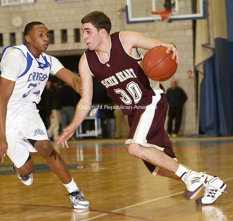WATERBURY, CT, 02/04/08- 020409BZ26- Sacred Heart's Joe Buzzuto (30) drives against Crosby's Marcus Robinson (31) during their game Wednesday night. <br /> Jamison C. Bazinet Republican-American