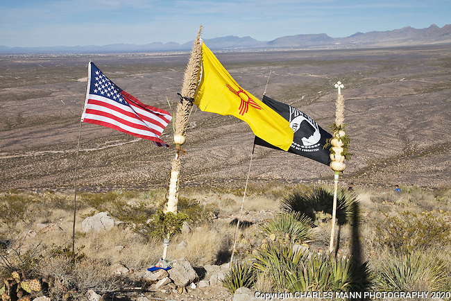 A US flag, a New Mexico flag an MIA flag and a traditional staff called a quiote all stand together on top of A Mountain during the annual December pilgrimage which is part of the  celebration of the Virgin of Guadalupe Feast Day at the village of Tortugas, near Las Cruces, New Mexico