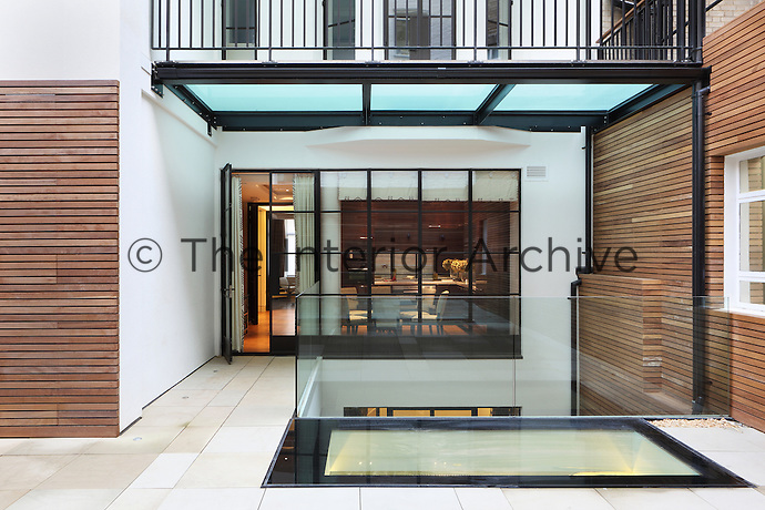 A modernised courtyard with a glass panel in the paving to allow light into the lower floor