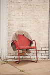 Red metal chair with rug hung over the back
