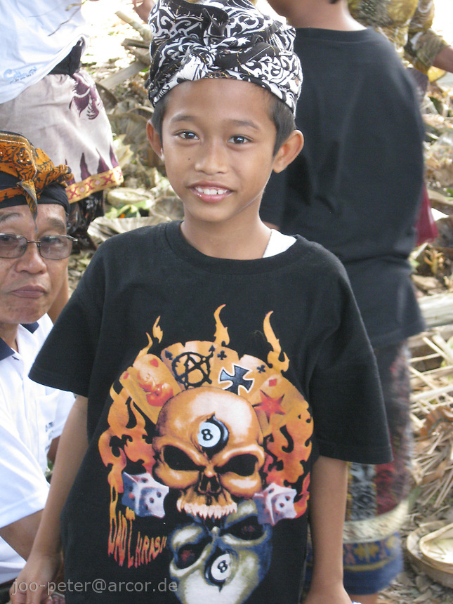 boy likes to dress up in his own style for cremation ceremonies in village Mas, Bali, archipelago Indonesia. It is very popular amoung boys to wear demon T-shirts on this occasion - it is believed to scare a bit the lower demons and keep off the place.