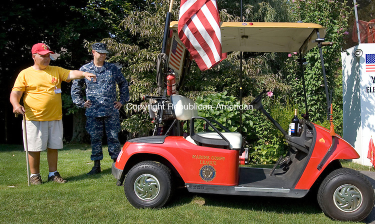 WATERBURY CT. 21 August 2013-082113SV01-From left, Mike Rinaldi of Waterbury shows Navy chaplain Bob Price his veteran golf cart at his home in Waterbury Wednesday. Chaplin, Price from the sub base in Groton blessed the golf cart that Rinaldi uses to welcome and remember veterans. <br /> Steven Valenti Republican-American
