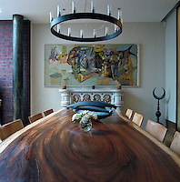 In a London dining room a circular chandelier hangs above the table where the swirling natural grain of the wood is an integral element of the design