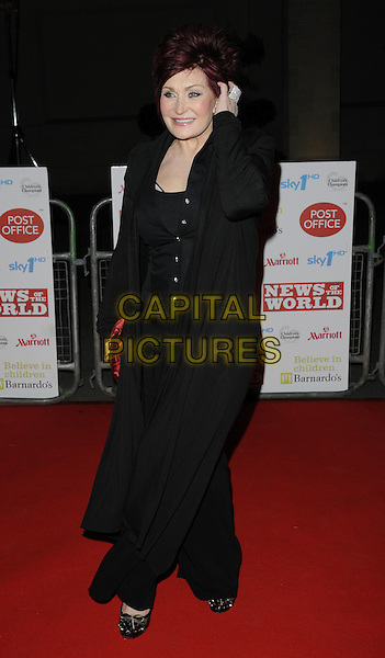 SHARON OSBOURNE .At the Children's Champions Awards 2010, Grosvenor House Hotel, Park Lane, London, England, UK, .March 3rd 2010..arrivals full length black long cardigan shirt trousers red clutch bag hand touching hair .CAP/CAN.©Can Nguyen/Capital Pictures.