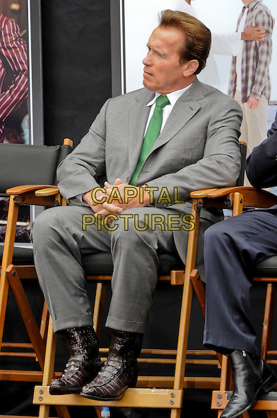 California Governor ARNOLD SCHWARZENEGGER.The opening of New York Street, the largest construction project in studio history, on the backlot at Universal Studios in Universal City, California, USA..May 27th, 2010   .full length grey gray suit green tie sitting brown boots cowboy crocodile animal leather profile.CAP/ROT.©Lee Roth/Capital Pictures