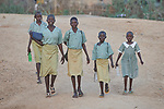 Girls walk to school in Kauda, a village in the Nuba Mountains of Sudan. The area is controlled by the Sudan People's Liberation Movement-North, and frequently attacked by the military of Sudan. The Catholic Church sponsors schools and health care facilities throughout the war-torn region.