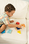 21 month old toddler boy at home playing with geometric shapes peg puzzle