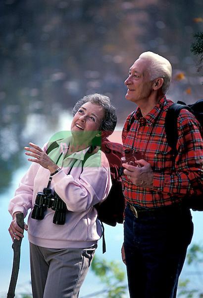 happy healthy elderly couple hiking in woods