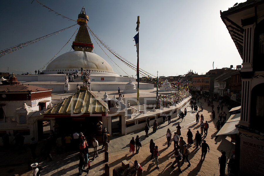 People walk and pray around Boudhanath or Bodnath Stupa, the largest stupa in Nepal, as the sun sets in Kathmandu.