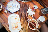 "Used skewers and empty drinks surround a group's table at He Wang Shi Chuan Chuan Xiang Huo Guo, a skewer-style hotpot restaurant popular with locals on Tiyu Road in Chongqing, China. The girl in white, who asked not to be named, said that it's one of their favorite places the hotpot flavor is so good.  ""We like the atmosphere. It's a typical Chongqing place: friends sit together and it's hot out and you all sweat together."" She works in real estate and thinks that places like this won't survive as neighborhoods develop."
