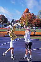 Fifth grade boys playing basketball on playground. Oregon.
