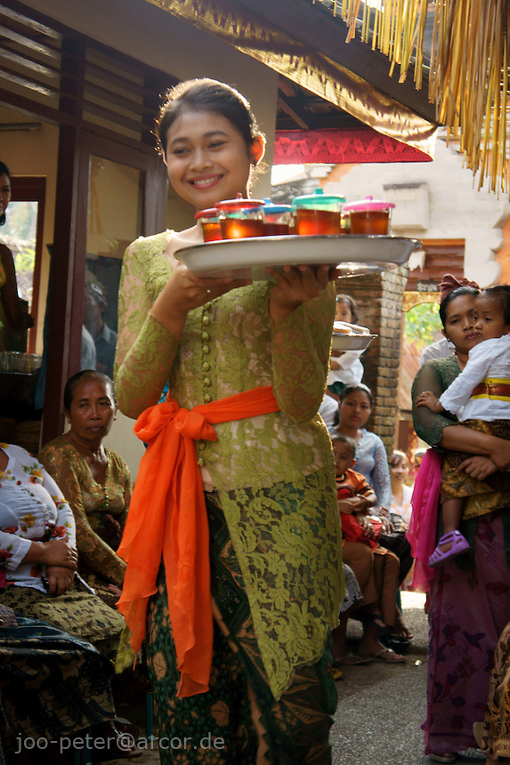girl serving tea for guests in ceremonies of Budiana family compound  two days before cremation takes place,,  September 15th  2011, Banjar Pande, Peliatan next to Ubud, Bali, archipelago Indonesia