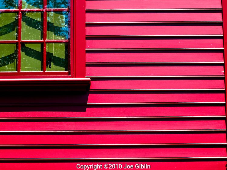 Green shutters in the window of a red colonial house with clapboard siding in Newport, RI. (Photo/Joe Giblin) no release