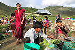 Farmers market on the roadside, with buddhist monk, Paro, Bhuthan...Bhutan the country that prides itself on the development of 'Gross National Happiness' rather than GNP. This attitude pervades education, government, proclamations by royalty and politicians alike, and in the daily life of Bhutanese people. Strong adherence and respect for a royal family and Buddhism, mean the people generally follow what they are told and taught. There are of course contradictions between the modern and tradional world more often seen in urban rather than rural contexts. Phallic images of huge penises adorn the traditional homes, surrounded by animal spirits; Gross National Penis. Slow development, and fending off the modern world, television only introduced ten years ago, the lack of intrusive tourism, as tourists need to pay a daily minimum entry of $250, ecotourism for the rich, leaves a relatively unworldly populace, but with very high literacy, good health service and payments to peasants to not kill wild animals, or misuse forest, enables sustainable development and protects the country's natural heritage. Whilst various hydro-electric schemes, cash crops including apples, pull in import revenue, and Bhutan is helped with aid from the international community. Its population is only a meagre 700,000. Indian and Nepalese workers carry out the menial road and construction work.