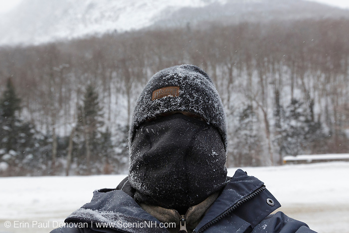 A winter hiker bundled up in cold weather gear while hiking in Franconia Notch State Park of the New Hampshire White Mountains on an extremely cold winter day.