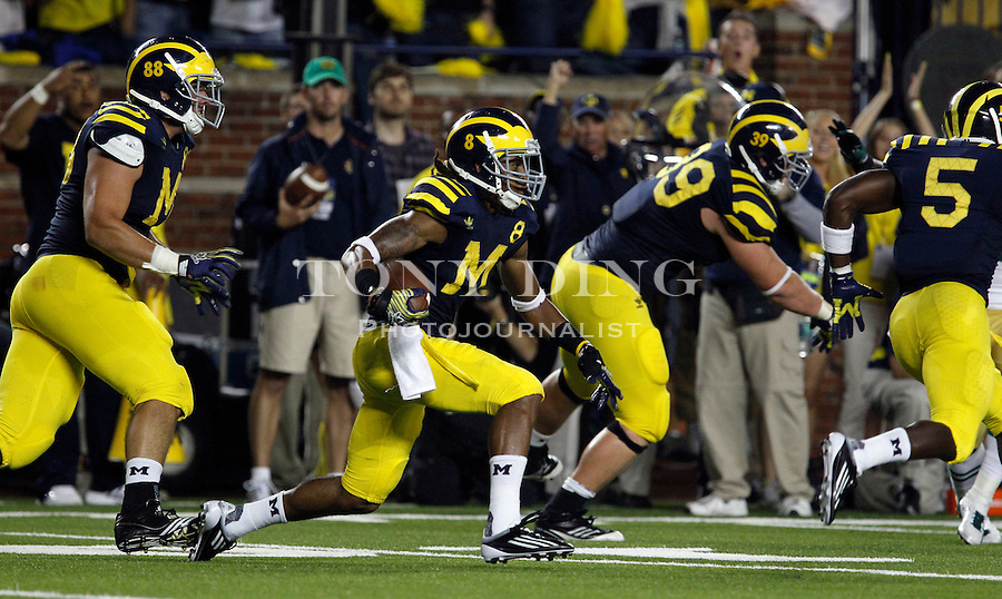 Michigan cornerback J.T. Floyd (8) returns an interception from Notre Dame quarterback Tommy Rees in the second quarter of an NCAA college football game, Saturday, Sept. 10, 2011, in Ann Arbor, Mich. Michigan won 35-31. (AP Photo/Tony Ding)