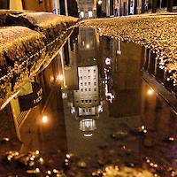 The U.S. Customs House reflects in a puddle on Strawberry Street in the Old City section of Philadelphia on December 16, 2012.