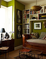An antique French daybed and a pair of portraits by Carlos Aponte are features of this studio/guest room