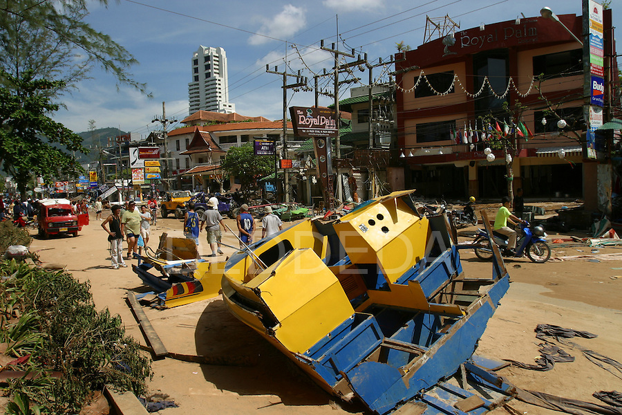 A boat that was washed ashore, sits on a main road at Patong Beach, on Phuket Island, Thailand, the day after the tsunami hit the coast. On December 26, 2004, a major earthquake generated tsunamis that ravaged coastlines from Southeast Asia to Africa. Approximately 275,000 people were killed and tens of thousands were left homeless, making it one of the deadliest natural disasters in modern history.