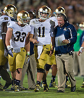 Brian Kelly talks with quarterback Tommy Rees (11) and running back Cam McDaniel (33).