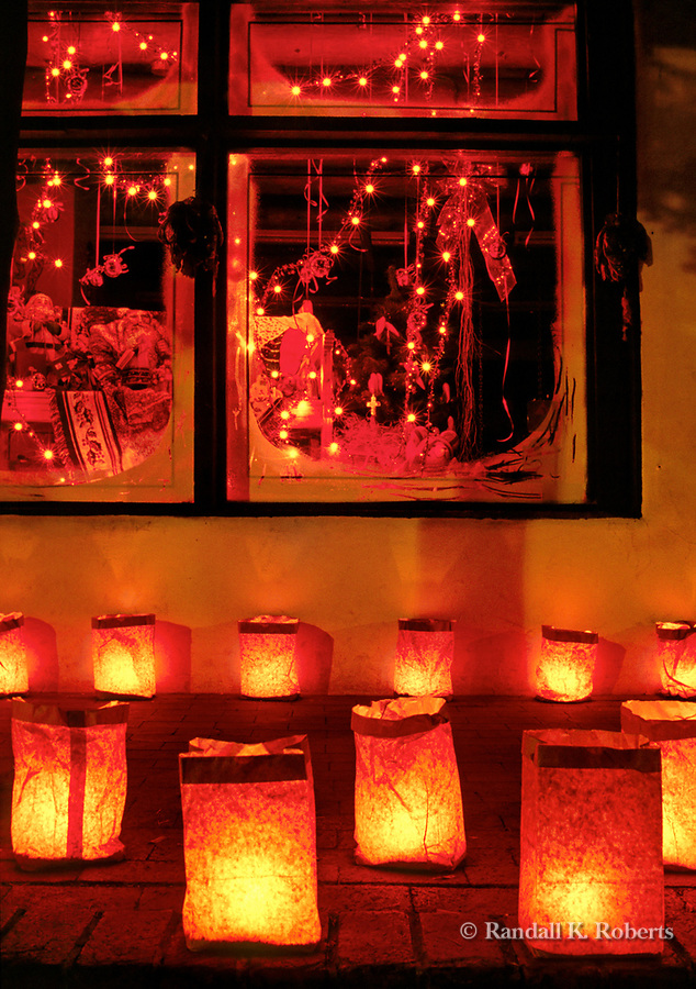 Christmas eve luminarias adorn the sidewalk outside a shop in Old Town Albuquerque, New Mexico
