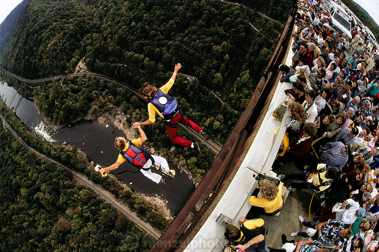 """BASE jumping from New River Gorge bridge, Bridge Day, West Virginia, USA. BASE jumping is the sport of using a parachute to jump from fixed objects. """"BASE"""" is an acronym that stands for the four categories of objects from which one can jump; (B)uilding, (A)ntenna (an uninhabited tower such as an aerial mast), (S)pan (a bridge, arch or dome), and (E)arth (a cliff or other natural formation). BASE jumping is much more dangerous than skydiving from aircraft and is currently regarded as a fringe extreme sport. -from Wikipedia."""
