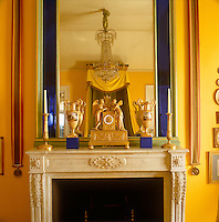 The ultramarine stained-glass inset of a large mirror is in stunning contrast to the bright yellow walls and ormolu clock on the mantelpiece of this bedrooom
