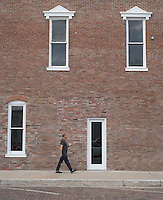 NWA Democrat-Gazette/J.T. WAMPLER Aaron Gist of Rogers walks past the old Opera House on S. 1st. Street in Rogers Tuesday Sept. 8, 2015. The building, which sits on the southwest corner of 1st Street and Walnut Street  was the center of Rogers social life in the late 19th and early 20th century. There has been a renovation project at the building since 2012.
