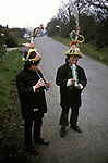 Biddy Boys 1970s. Killorglin  Co Kerry Ireland. February 2nd festival to celebrate the Celtic Saint Bridgid. Two young Biddy Boys playing a Penny Whistle and a ?. They are walking from house to house wearing the traditional straw conical hat collecting money...