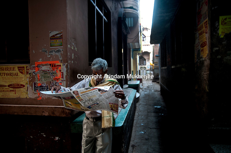 Indian man reads newspaper at a lane in Varanasi, Uttar Pradesh, India.