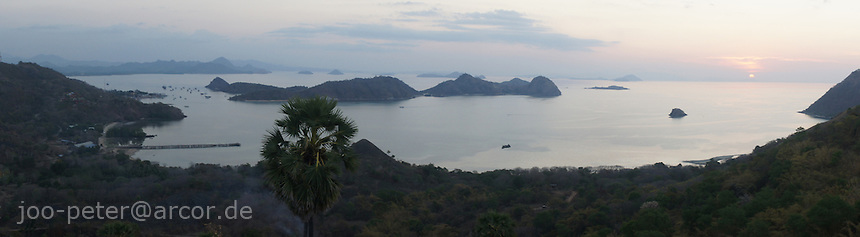 view on harbour Labuan Bajo at sunset, looking west in  direction of Komodo island national parc area, island  Flores in archipelago of Indonesia