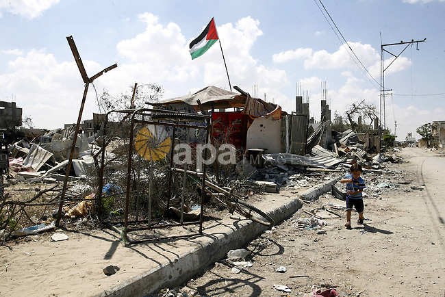 "A Palestinian boy plays near a destroyed house in Khan Yunis in the southern Gaza Strip on September 11, 2014. Israel's deputy foreign minister,Tzahi Hanegbi , warned that Hamas was likely to resume ""violence"" if it feels it has made no political gains from upcoming talks in Cairo. Photo by Abed Rahim Khatib"