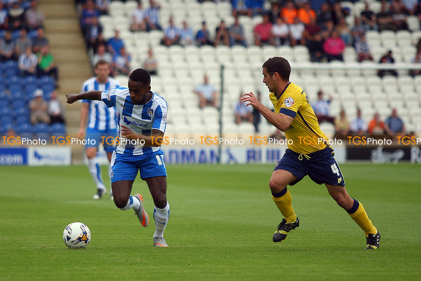 Gavin Massey of Colchester United runs with the ball as Sean McAllister of Scunthorpe United looks on during Colchester United vs Scunthorpe United, Sky Bet League 1 Football at the Weston Homes Community Stadium, Colchester, England on 29/08/2015