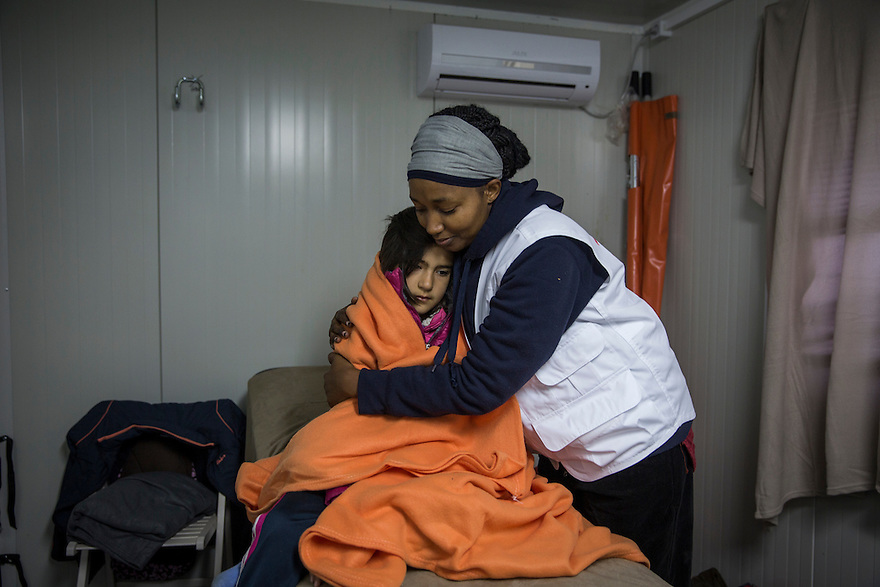 Josephine Makena, nurse team leader for MSF medical team at work in Idomeni, with a patient, a 10 year-old girl from Iran named Nagim. Greece, where several thousand people were stranded in December, unable to cross into Macedonia due to nationality restrictions put in place by several Balkan nations. Meanwhile many thousands of Syrians, Afghans and Iraqis passed through the border each day after having their documents checked by Macedonian border police.