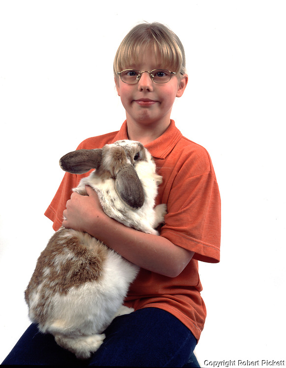 Young Girl Holding Pet Rabbit, Lop Lemon & White Colour, aged 10 years old, domestic, white background, cut out, studio