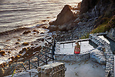 USA, California, Big Sur, Esalen, a woman sits on the edge of the hot spring at the Baths and takes in the evening view, the Esalen Institute