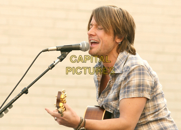 KEITH URBAN.is joined by Verizon Wireless and Samsung Mobile as he makes an in-store appearance for his fans at the Verizon Wireless store in Pasadena, California, USA, November 21st 2009                                                                   .half length music concert gig live on stage grey gray brown plaid checked check shirt microphone playing tattoo bracelets singing profile guitar .CAP/RKE/DVS.©DVS/RockinExposures/Capital Pictures