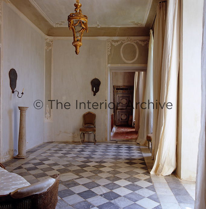 The grand hall has a black and white marble floor and gilt chandelier