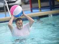 NWA Democrat-Gazette/FLIP PUTTHOFF <br /> POOL PARTY<br /> Nick Spainhower tosses a ball on Wednesday Aug. 8 2019 during a water aerobics session at the Gravette city pool. The Billy V. Hall Senior Activity and Wellness Center in Gravette has offered water aerobics through the summer. The final session will be Friday. Once Gravette schools start on Aug. 14, the city pool will be open Saturdays and Sundays only through Labor Day weekend.