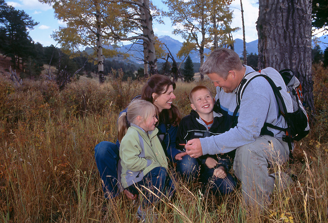 Family of four examine fall-color aspen leaf, Rocky Mtn Nat'l Park, CO