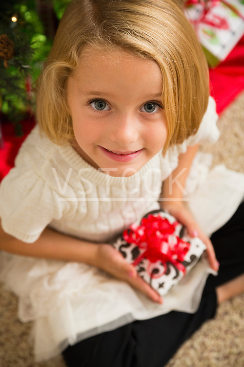 Portrait of girl (6-7) holding Christmas present