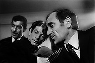 """October 28th, 1966. Hotel Waldorf Astoria, Manhattan, NYC. In the room of Maurice Chevalier after his performance at the Show """"April in Paris"""". On the picure we can see: Jose Reyes singing, at the guitar Manitas de Plata and Charles Aznavour."""